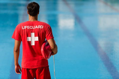 Rear view of male lifeguard with emergency equipment in red uniform watching swimming pool.